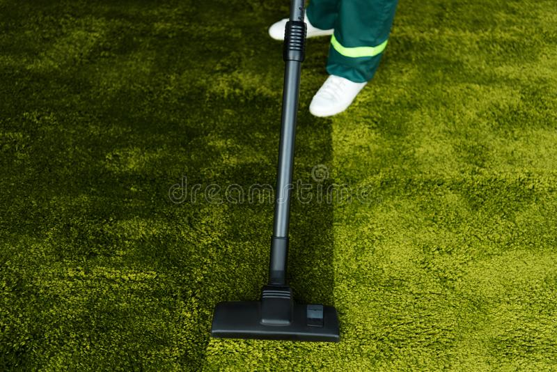 χαμηλό τμήμα του προσώπου που καθαρίζει τον πράσινο τάπητα με το κενό στοκ φωτογραφία