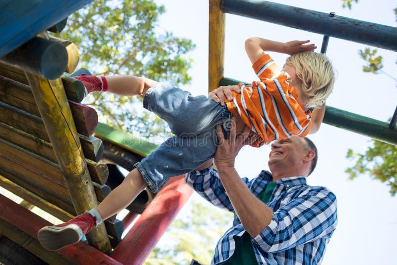 Χαμηλή άποψη γωνίας του βοηθώντας γιου πατέρων στο παιχνίδι στη γυμναστική ζουγκλών στοκ φωτογραφίες με δικαίωμα ελεύθερης χρήσης