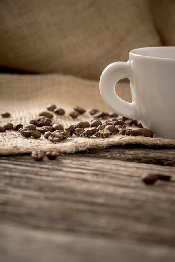 Χαμηλή άποψη γωνίας των φασολιών καφέ που διασκορπίζεται στο ύφασμα λινού που βρίσκεται επάνω στοκ φωτογραφία