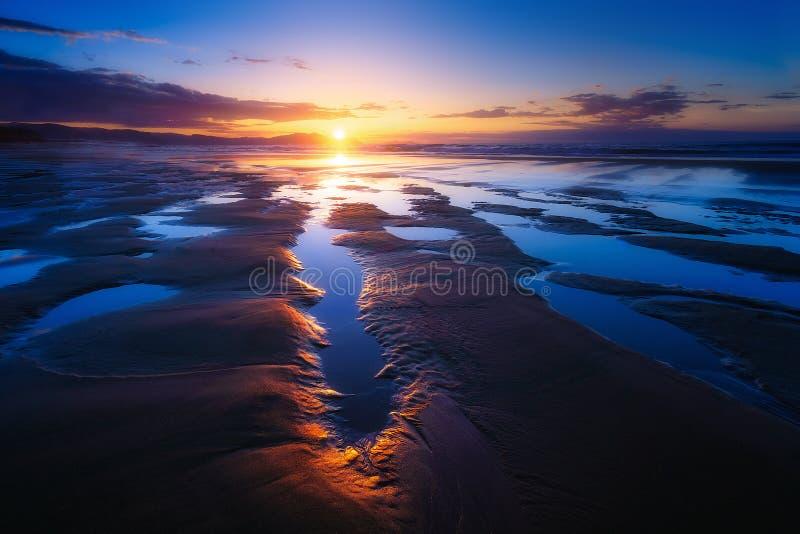 Χαμηλή παλίρροια στην παραλία με τις λακκούβες στο ηλιοβασίλεμα στοκ φωτογραφία με δικαίωμα ελεύθερης χρήσης