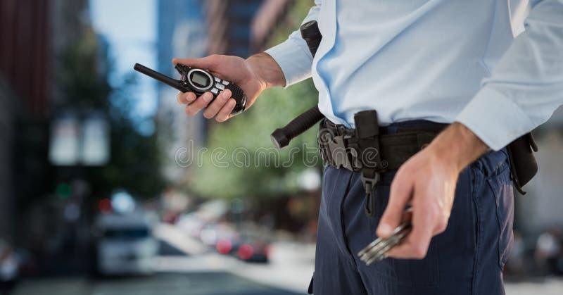 Χαμηλότερο σώμα φρουράς ασφάλειας με την ομιλούσα ταινία walkie ενάντια στη μουτζουρωμένη οδό στοκ φωτογραφία