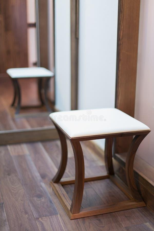 Χαμηλό τετραγωνικό σκαμνί με ένα γεμισμένο κάθισμα σε ένα σύγχρονο εσωτερικό στοκ εικόνες
