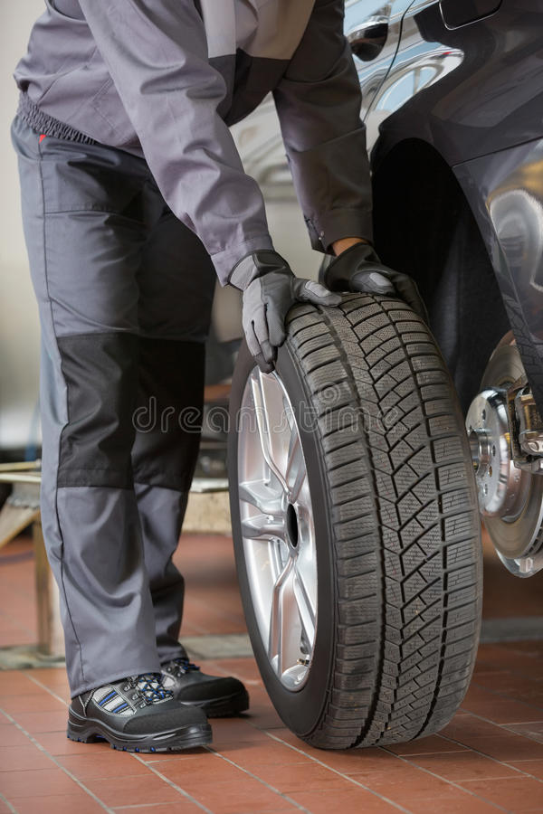 Χαμηλό τμήμα της ρόδας του αυτοκινήτου καθορισμού επισκευαστών στο εργαστήριο στοκ φωτογραφία με δικαίωμα ελεύθερης χρήσης