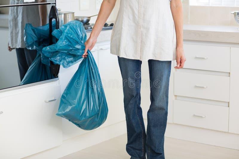 Χαμηλό τμήμα της φέρνοντας τσάντας απορριμάτων γυναικών στην κουζίνα στοκ φωτογραφίες