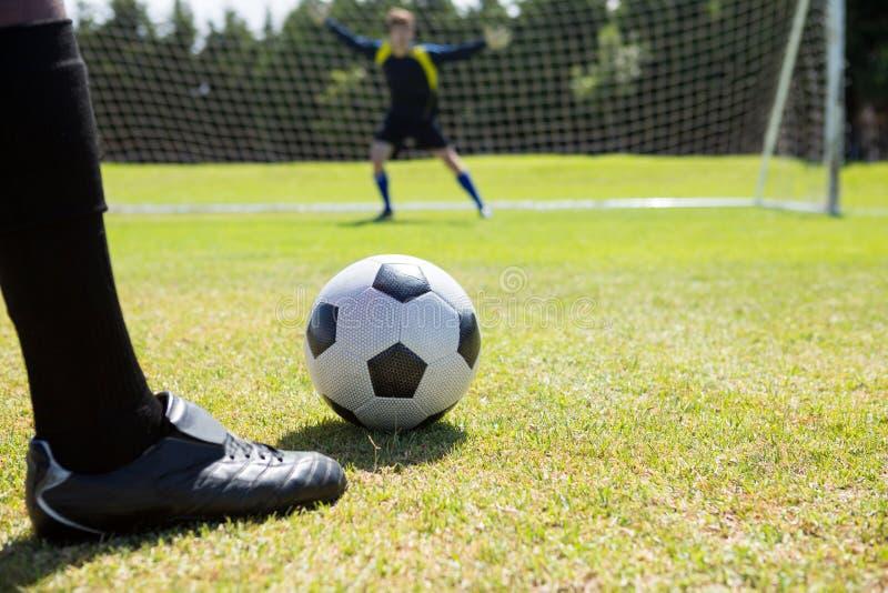 Χαμηλό τμήμα του ποδοσφαιριστή με τη σφαίρα ενάντια στον τερματοφύλακας στοκ φωτογραφία με δικαίωμα ελεύθερης χρήσης