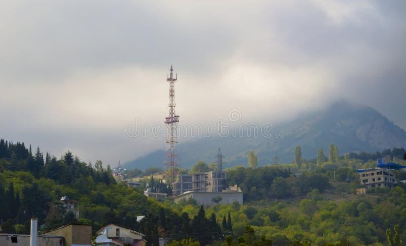 Χαμηλό cloudiness πέρα από τα βουνά και τα σπίτια στοκ φωτογραφίες