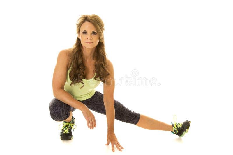 Χαμηλό lunge ηλικιωμένων γυναικών πράσινο πουκάμισο στοκ εικόνες