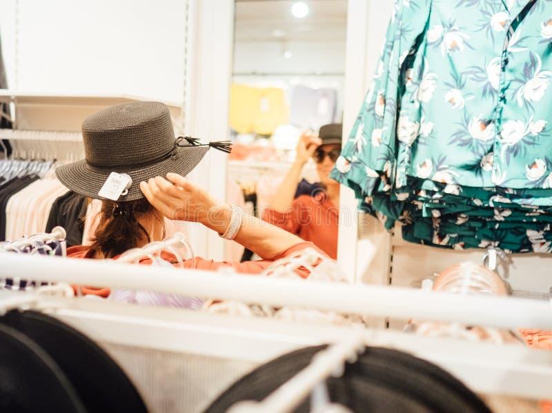 Χαμογελαστή γυναίκα δοκιμάζει το νέο καπέλο κοιτάζοντας τον καθρεφτισμό 1 στοκ εικόνα με δικαίωμα ελεύθερης χρήσης