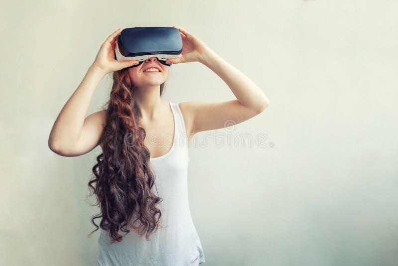 Χαμογελαστή νεαρή γυναίκα που φορά με τη χρήση των γυαλιών VR εικονικής  στοκ φωτογραφία