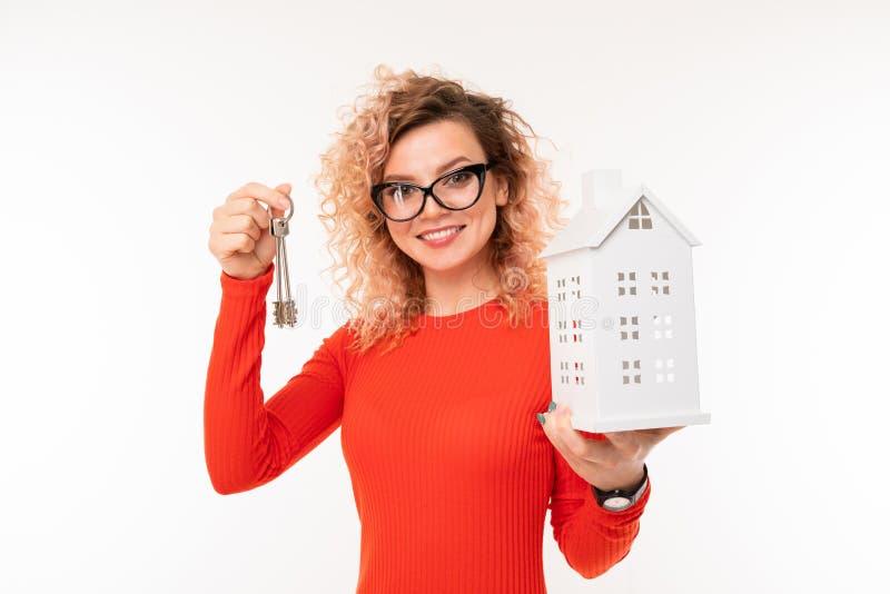 Χαμογελαστή ξανθιά κοπέλα με διάταξη σπιτιού και πλήκτρα σε λευκό φόντο στοκ φωτογραφία