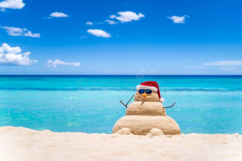 Χαμογελαστός αμμώδης χιονάνθρωπος με κόκκινο καπέλο άγιος βασίλης στην παραλία της καραϊβικής με όμορφο ουρανό Ιδέα διακοπών για  στοκ φωτογραφία με δικαίωμα ελεύθερης χρήσης