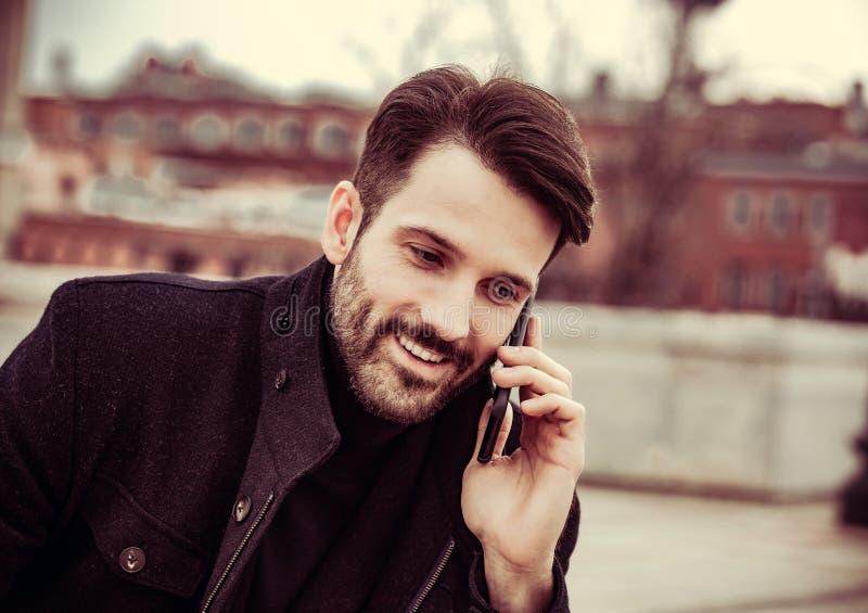 Χαμογελαστός επιχειρηματίας με ρούχα μόδας που μιλάει σε κινητό τηλέφωνο στο εξωτερικό φθινοπωρινό φόντο Κατακόρυφος στοκ εικόνα με δικαίωμα ελεύθερης χρήσης