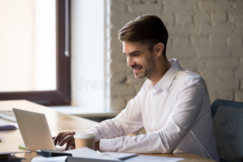 Χαμογελαστός επιχειρηματίας που χρησιμοποιεί φορητό υπολογιστή, εργάζεται στο διαδίκτυο ή γράφει email στοκ εικόνες