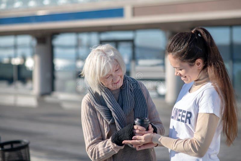 Χαμογελαστός ευγενικός εθελοντής που υποστηρίζει φτωχούς άστεγους συνταξιούχους στοκ εικόνες