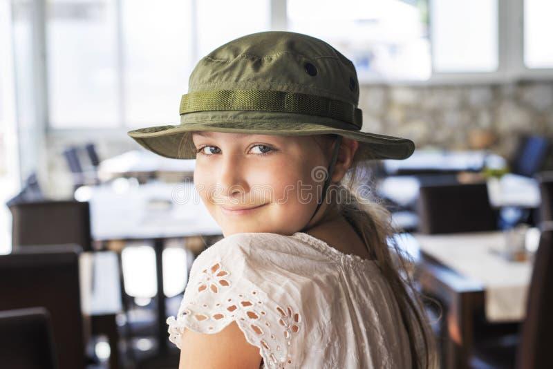 Χαμογελαστό κορίτσι με καπέλο στο εστιατόριο στοκ εικόνες με δικαίωμα ελεύθερης χρήσης