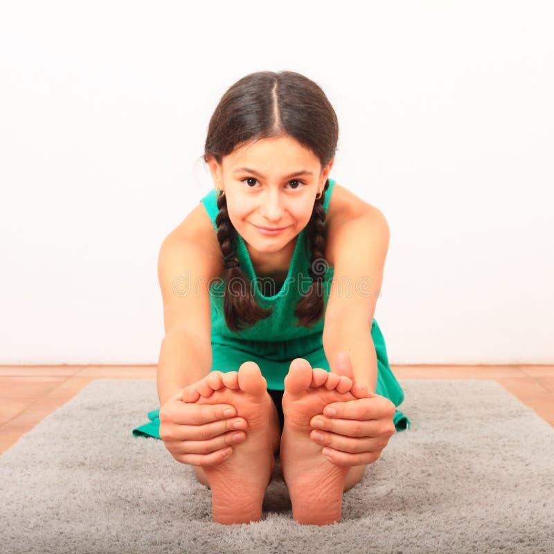 Χαμογελαστό κορίτσι που εξασκεί τη γιόγκα - καθισμένη με δίπλωμα προς τα εμπρός στοκ φωτογραφίες με δικαίωμα ελεύθερης χρήσης