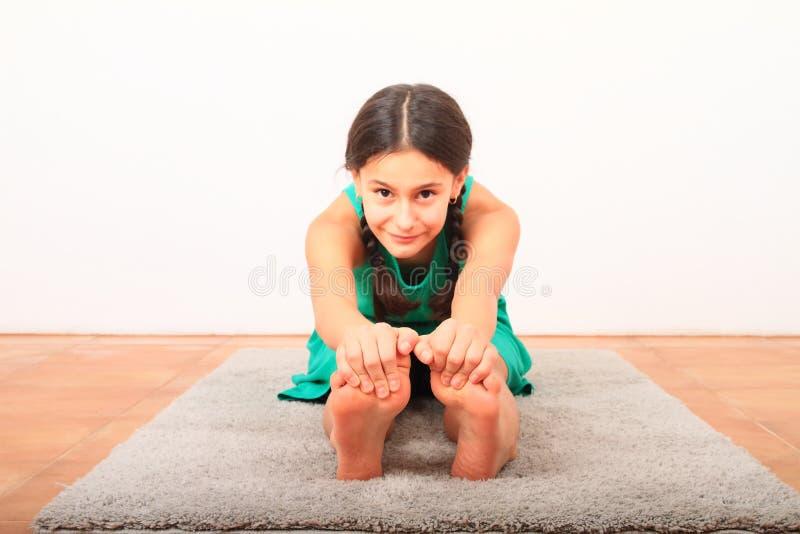 Χαμογελαστό κορίτσι που εξασκεί τη γιόγκα - καθισμένη με δίπλωμα προς τα εμπρός στοκ εικόνες