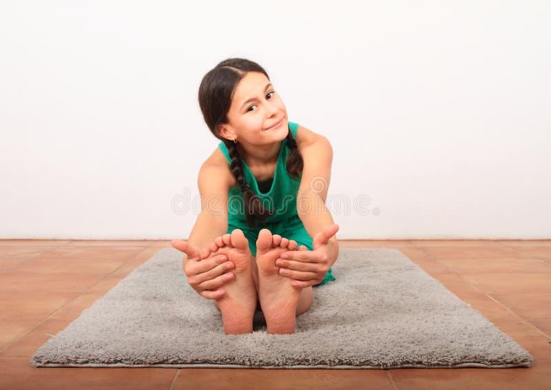 Χαμογελαστό κορίτσι που εξασκεί τη γιόγκα - καθισμένη με δίπλωμα προς τα εμπρός στοκ εικόνες με δικαίωμα ελεύθερης χρήσης