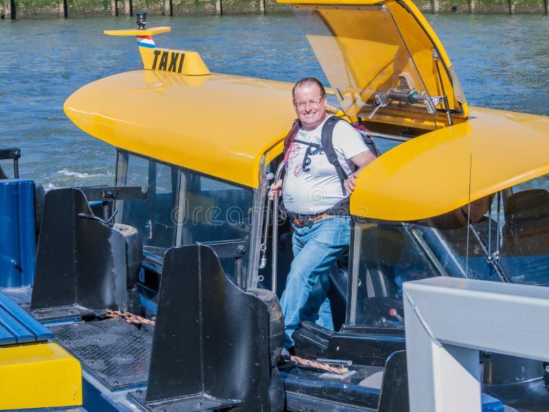 Χαμογελώντας άτομο με τα περιστασιακά ενδύματα που αποβηβάζει από μια βάρκα ταξί στοκ εικόνες