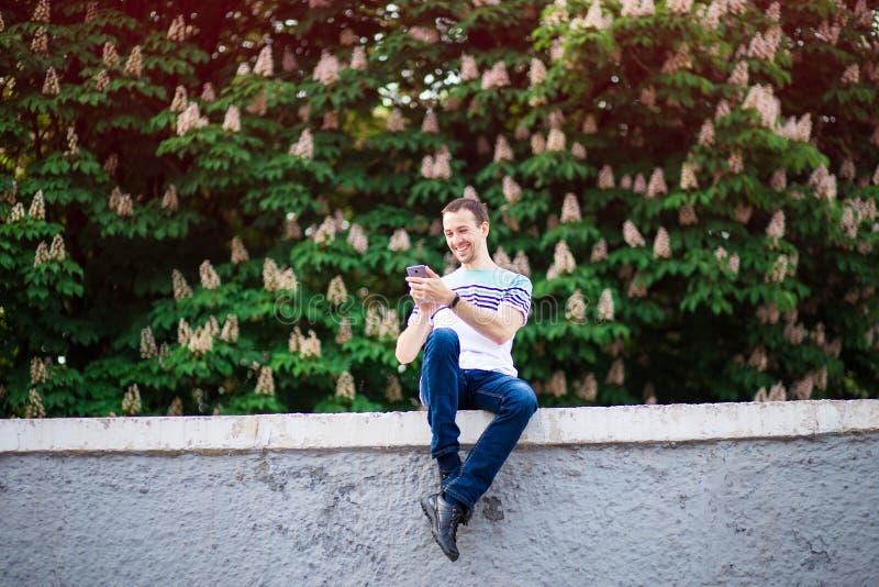 Χαμογελώντας άτομο με τη διαθέσιμη συνεδρίαση χεριών smartphone στην οδό και τη χρησιμοποίηση του αγγελιοφόρου στοκ φωτογραφία