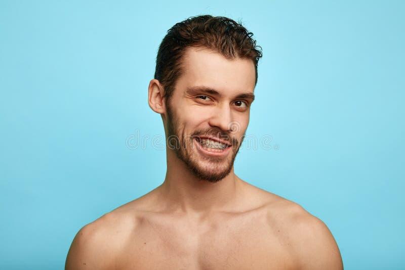 Χαμογελώντας άτομο που παρουσιάζει δόντια του, στηρίγματα στη κάμερα στοκ εικόνα
