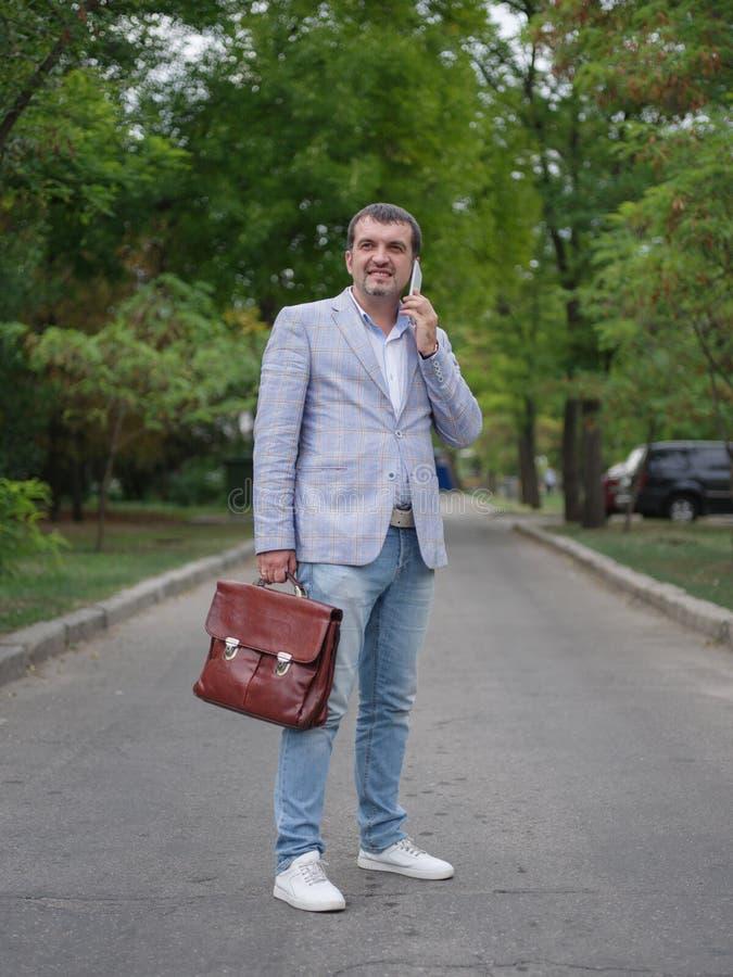 Χαμογελώντας άτομο που περπατά σε ένα θολωμένο υπόβαθρο πάρκων Ένας επιχειρησιακός υπάλληλος που μιλά σε ένα τηλέφωνο Οικονομική  στοκ εικόνες με δικαίωμα ελεύθερης χρήσης