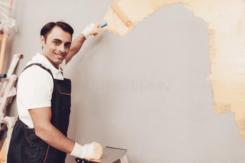 Χαμογελώντας άτομο σε Labber στον ομοιόμορφο γκρίζο τοίχο χρωμάτων στοκ εικόνες