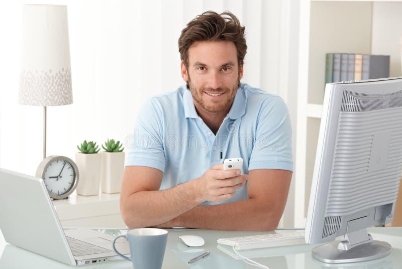 Χαμογελώντας άτομο στο γραφείο με το κινητό τηλέφωνο στοκ εικόνα