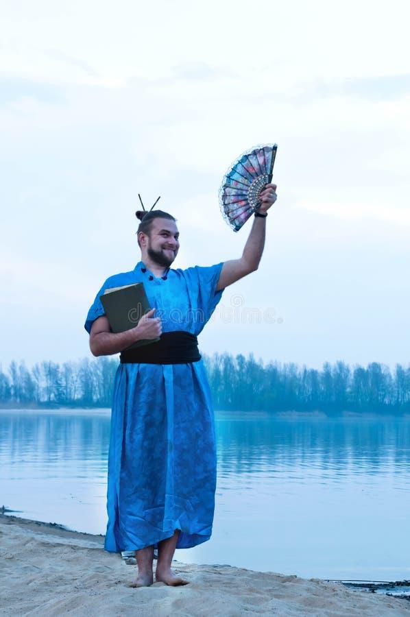 Χαμογελώντας άτομο στο μπλε κιμονό με το κουλούρι τρίχας που στέκεται και που κρατά τον ανεμιστήρα βιβλίων και χεριών στοκ φωτογραφίες με δικαίωμα ελεύθερης χρήσης
