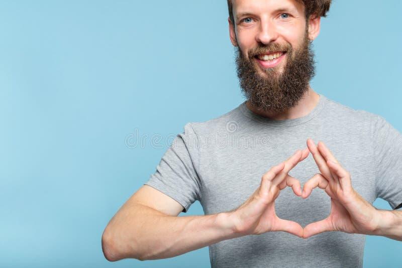Χαμογελώντας άτομο συγκίνησης αγάπης που κατασκευάζει την καρδιά να διαμορφώσει τα χέρια στοκ εικόνες με δικαίωμα ελεύθερης χρήσης