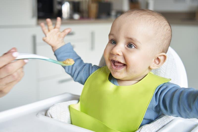 Χαμογελώντας αγοράκι οχτώ μηνών βρεφών στο σπίτι στην υψηλή έδρα που ταΐζεται τα στερεά τρόφιμα από τη μητέρα με το κουτάλι στοκ φωτογραφία με δικαίωμα ελεύθερης χρήσης