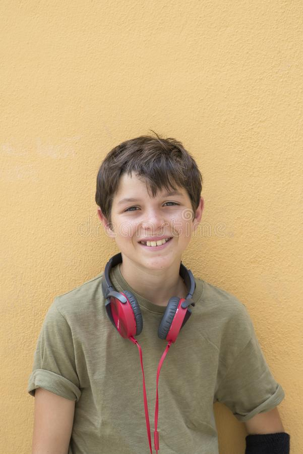 Χαμογελώντας αγόρι εφήβων που θέτει υπαίθρια Εξέταση τη κάμερα με το headpho στοκ εικόνες