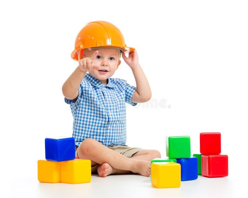 Χαμογελώντας αγόρι παιδιών με τους σκληρούς κύβους παιχνιδιού καπέλων, που απομονώνεται στο λευκό στοκ εικόνα με δικαίωμα ελεύθερης χρήσης