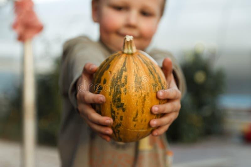 Χαμογελώντας αγόρι που στέκεται με τη μεγάλη κίτρινη κολοκύθα στα χέρια στοκ φωτογραφία