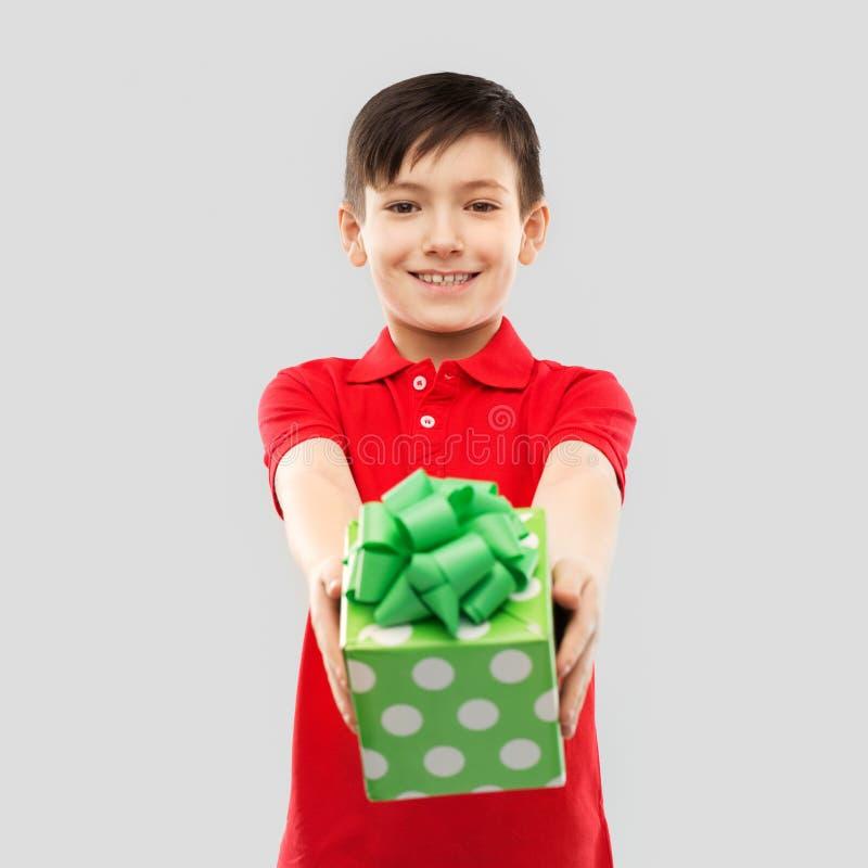 Χαμογελώντας αγόρι στην κόκκινη μπλούζα με το κιβώτιο δώρων γενεθλίων στοκ εικόνες με δικαίωμα ελεύθερης χρήσης