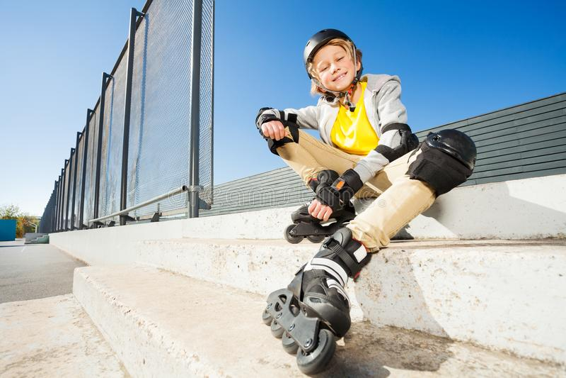 Χαμογελώντας αγόρι στις λεπίδες κυλίνδρων που κάθεται στα σκαλοπάτια στοκ εικόνες