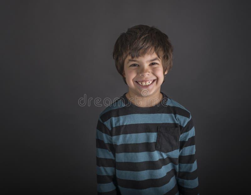 Χαμογελώντας αγόρι στο ριγωτό πουκάμισο στοκ εικόνες