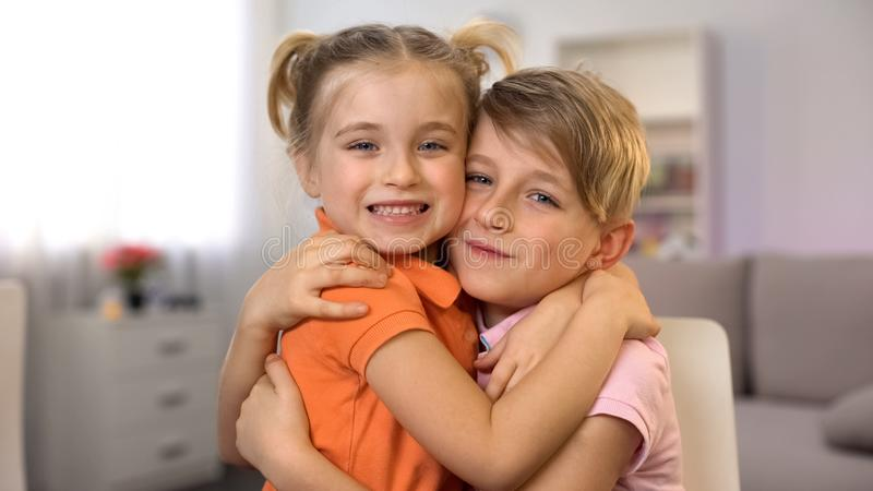 Χαμογελώντας αδελφή και αδελφός που αγκαλιάζουν και που εξετάζουν τη κάμερα στο σπίτι, ευτυχία στοκ φωτογραφία με δικαίωμα ελεύθερης χρήσης