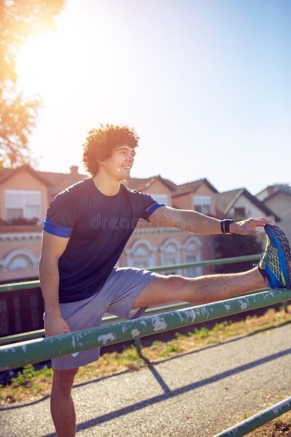 Χαμογελώντας αθλητικός δρομέας που κάνει την τεντώνοντας άσκηση, που προετοιμάζεται για στοκ εικόνες