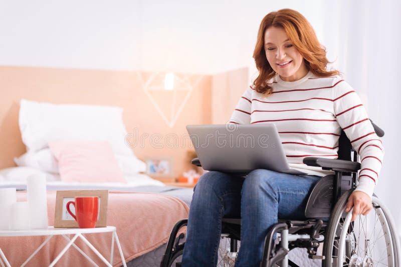Χαμογελώντας ανίκανη γυναίκα που εργάζεται στο lap-top της στοκ εικόνες