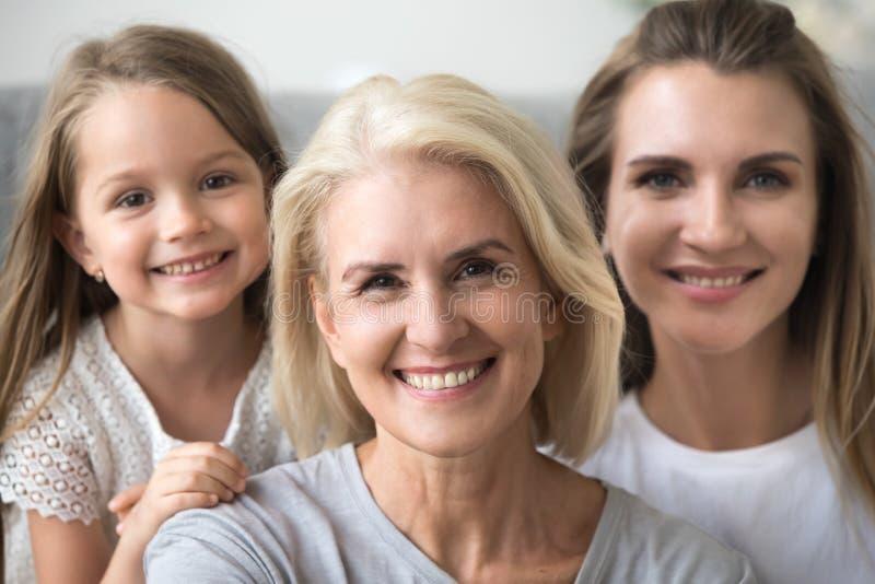 Χαμογελώντας ανώτερη γιαγιά που εξετάζει τη κάμερα με την κόρη και το γ στοκ φωτογραφία με δικαίωμα ελεύθερης χρήσης