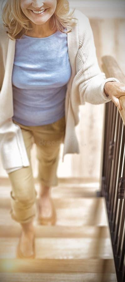Χαμογελώντας ανώτερη γυναίκα που αναρριχείται επάνω στο σπίτι στοκ εικόνες