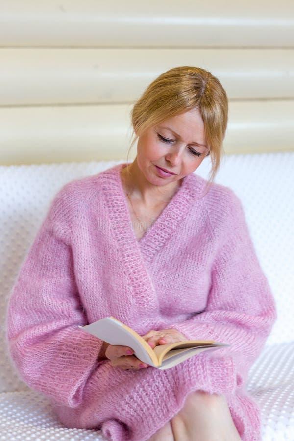 Χαμογελώντας ανώτερη γυναίκα που διαβάζει ένα βιβλίο στο σπίτι στοκ φωτογραφία