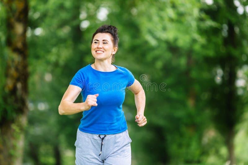 Χαμογελώντας ανώτερη γυναίκα που τρέχει στο πάρκο Καλυπτόμενη από ρείκια έννοια τρόπου ζωής Copyspace στοκ φωτογραφία με δικαίωμα ελεύθερης χρήσης