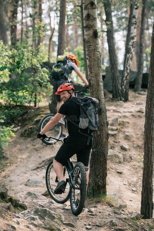 χαμογελώντας αρσενικός ακραίος ποδηλάτης που οδηγά στο ποδήλατο βουνών με το φίλο στοκ φωτογραφίες με δικαίωμα ελεύθερης χρήσης