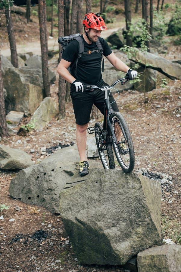 χαμογελώντας αρσενικός ακραίος ποδηλάτης στο προστατευτικό κράνος που στέκεται με το ποδήλατο βουνών στην πέτρα στοκ φωτογραφία