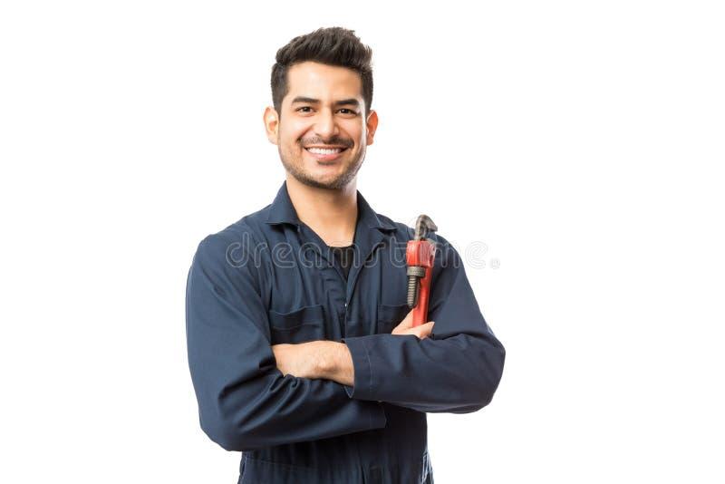 Χαμογελώντας αρσενικός υδραυλικός με τα μόνιμα όπλα γαλλικών κλειδιών σωλήνων που διασχίζονται στοκ εικόνες