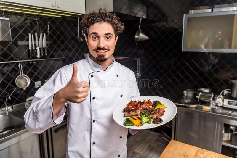 χαμογελώντας αρχιμάγειρας που παρουσιάζει τον αντίχειρα και κράτημα των μαγειρευμένων λαχανικών ελεύθερη απεικόνιση δικαιώματος