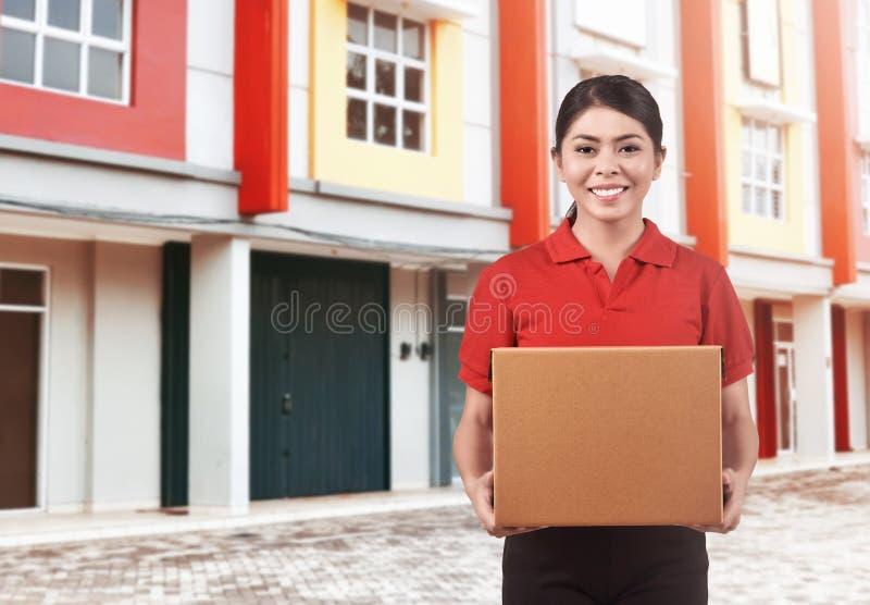 Χαμογελώντας ασιατική γυναίκα αγγελιαφόρων που παραδίδει τη συσκευασία στοκ εικόνα με δικαίωμα ελεύθερης χρήσης