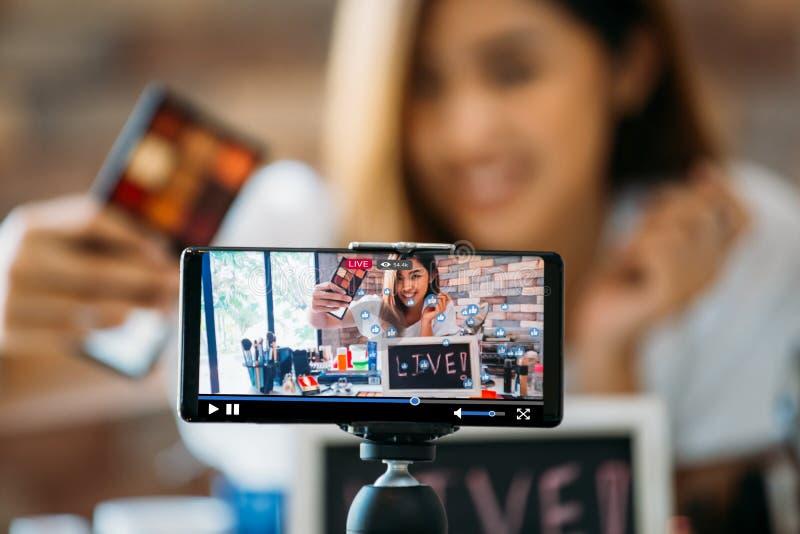 Χαμογελώντας ασιατική γυναίκα που παρουσιάζει σκιές ματιών στην επίδειξη του smartphone στοκ εικόνες με δικαίωμα ελεύθερης χρήσης